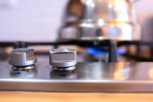 Włączenie kuchenki gazowej w kuchni. metalowy, srebrny czajniczek rozgrzewający się na gazie.