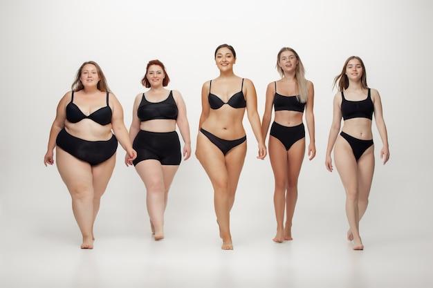 Włączenie. portret pięknych młodych kobiet o różnych kształtach pozowanie na białym tle. szczęśliwe modelki. pojęcie pozytywnego ciała, piękna, mody, stylu, feminizmu. różnorodność.