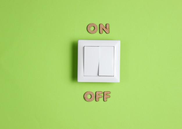 Włącznik światła z włączonym napisem na zielonej powierzchni