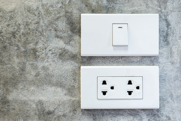 Włączony biały plastikowy włącznik światła i białe gniazdka elektryczne na betonowej ścianie, pokój w stylu loftu.