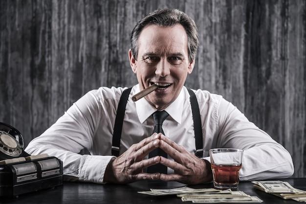 Władza jest w jego rękach. uśmiechnięty starszy mężczyzna w koszuli i szelkach siedzi przy stole i pali cygaro, podczas gdy obok niego leży mnóstwo pieniędzy