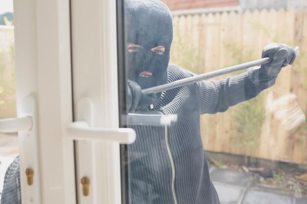 Włamywacz otwiera drzwi z łomem