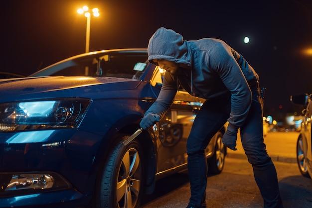Włamywacz przebija oponę, wandalizm, chuligan. zakapturzony bandyta psuje pojazd na parkingu. napad samochodowy, przestępstwo samochodowe