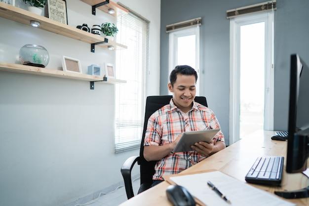 Właściciel biznesu relaksuje używać pastylkę przy jego biurem