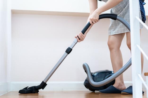 Właściciel domu za pomocą maszyny próżniowej do czyszczenia drewnianej podłogi.