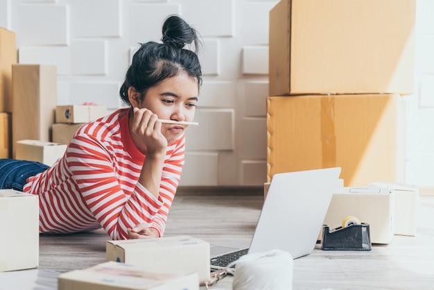 Właściciel firmy azjatyckiej pracujący w domu z pudełkiem do pakowania w miejscu pracy