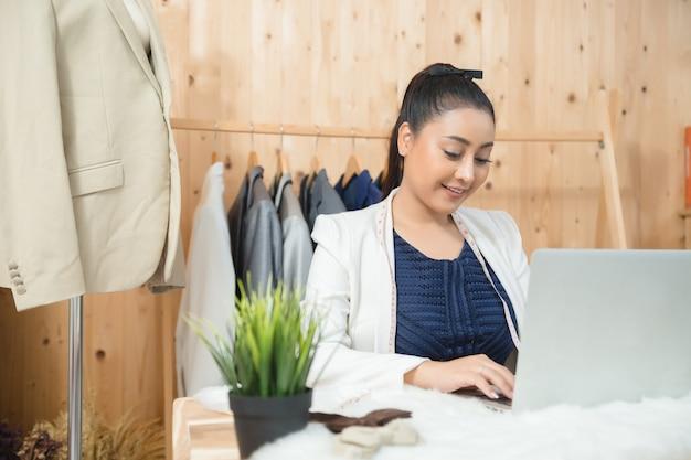 Właściciel firmy kobieta pracuje w swoim sklepie krawieckim