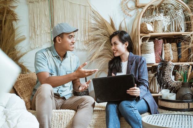 Właściciel firmy rzemieślniczej i klient, rozmawiając gestami rąk podczas korzystania z laptopa w sklepie rzemieślniczym z rzemiosłem
