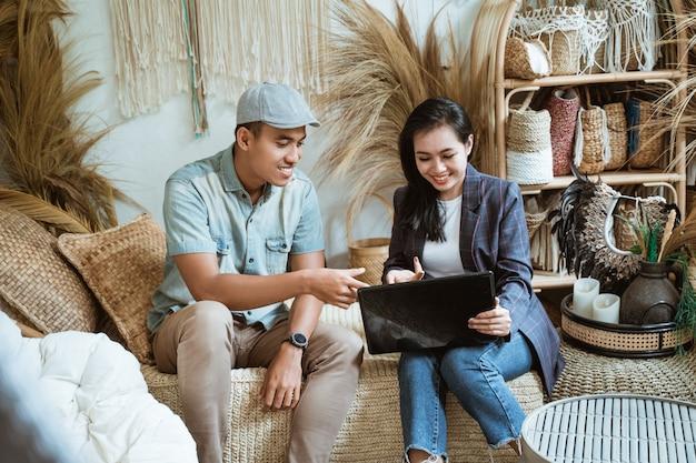 Właściciel firmy rzemieślniczej i klient używają laptopa w sklepie rzemieślniczym z rzemiosłem