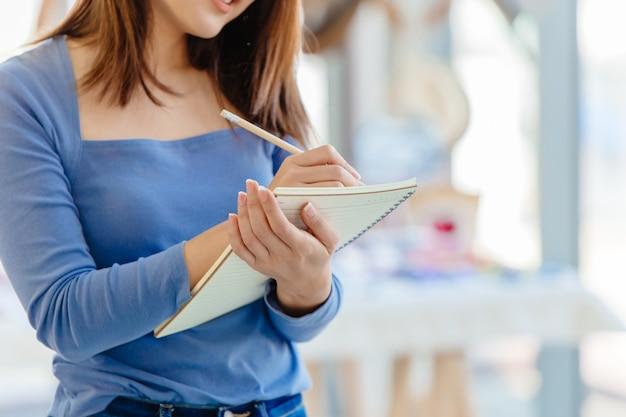Właściciel firmy sprawdza zapasy magazynowe w celu zamówienia nowych produktów do raportu kierownika sklepu z modą sme