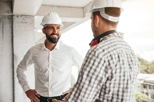 Właściciel firmy, uśmiechając się i rozmawiając z męskim konstruktorem