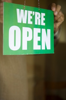 Właściciel firmy wiesza otwarty znak przy szklanym drzwi