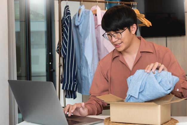 Właściciel firmy z azji, pracujący w domu z opakowaniem swojego sklepu internetowego, przygotowuje się do dostarczania produktów klientom