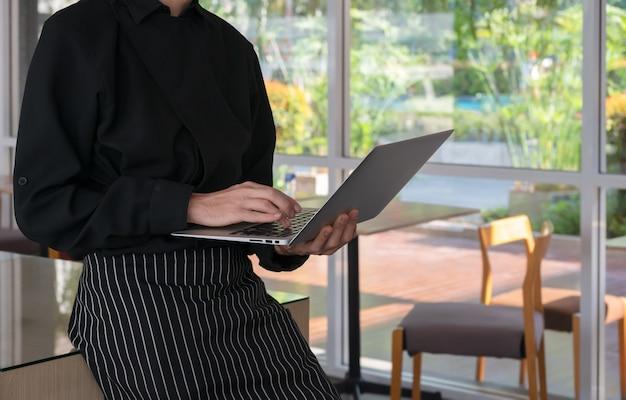 Właściciel kawiarni barista pracuje na laptopie stojąc w kawiarni, licząc zysk