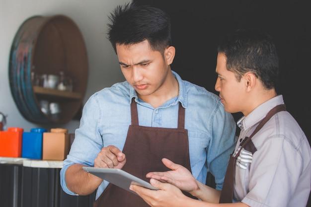 Właściciel kawiarni dyskutuje z jego pracownikiem używa pastylkę
