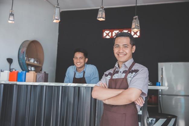 Właściciel kawiarni stojący ze skrzyżowanymi rękami