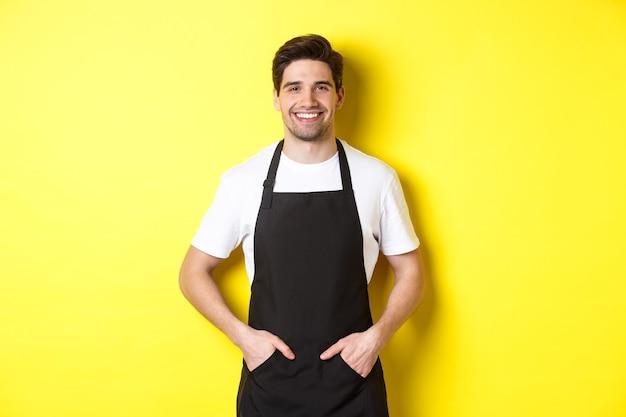 Właściciel kawiarni ubrany w mundur i uśmiechnięty, stojący nad żółtą ścianą