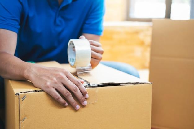 Właściciel małej firmy internetowej pakuje w karton.