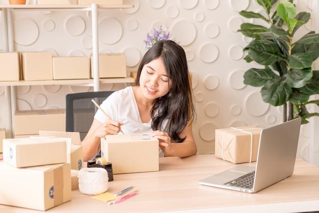 Właściciel małej firmy, kobieta sprawdza zamówienie w laptopie