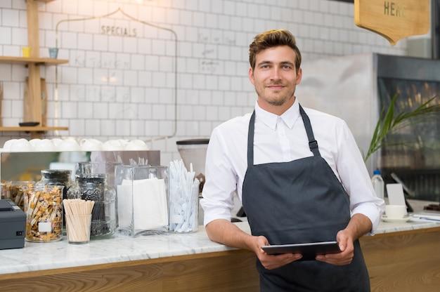 Właściciel małej firmy, odnoszący sukcesy, trzymając cyfrowy tablet