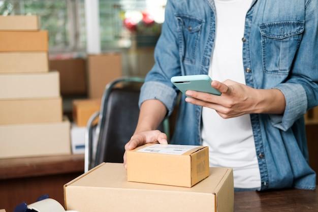 Właściciel małej firmy online. młody startupowy przedsiębiorca, właściciel małej firmy online, pracujący w domu, w sytuacji pakowania i dostawy.