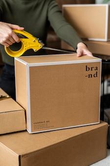 Właściciel małej firmy pakujący pudełka z produktami do dostawy