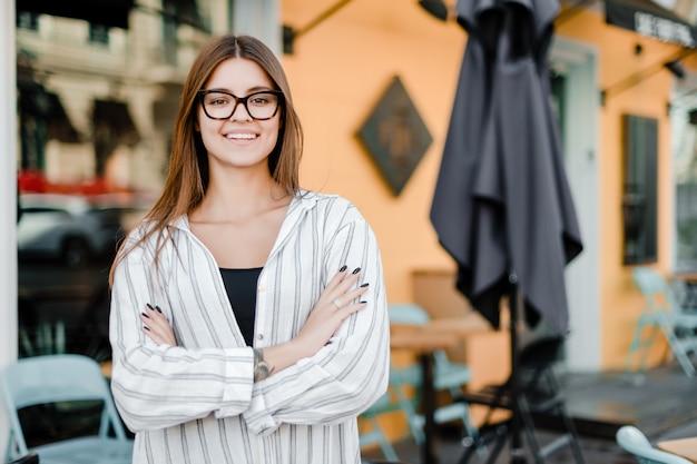 Właściciel małej firmy przed kawiarnią z uśmiechem