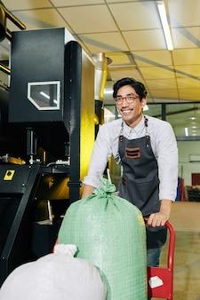 Właściciel palarni pchający wózek z fasolą