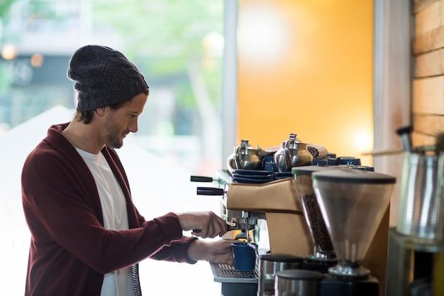 Właściciel robi filiżankę kawy w ekspresie do kawy