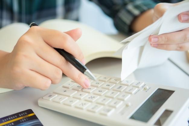 Właściciel siedzący przy obliczaniu rocznego podatku bransoletki z obrotu aby zmniejszyć