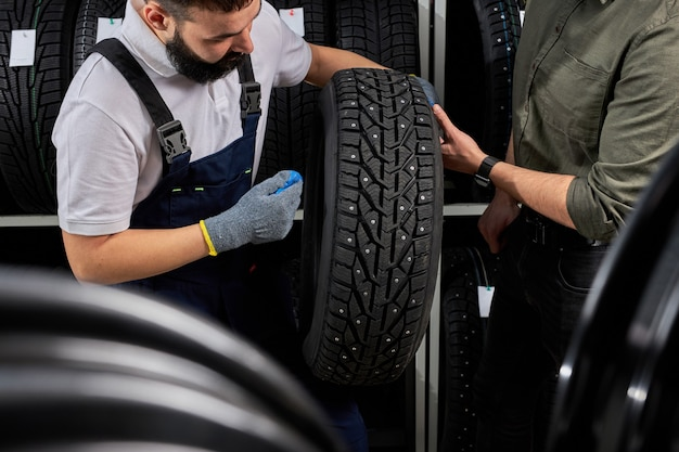Właściciel sklepu garażowego trzyma najlepszą oponę w supermarkecie i mierzy gumowe koło samochodu. w miejscu pracy