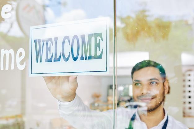 Właściciel sklepu nakleja znak powitalny