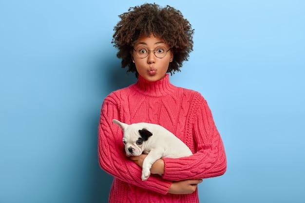 Właściciel słodkiego psa z kręconymi włosami niesie białego szczeniaka z czarnym uchem
