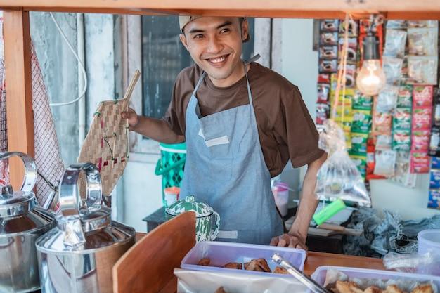 Właściciel stoiska z wózkiem z bliska trzyma ręczny wentylator, aby włączyć kuchenkę na wózku angkringan