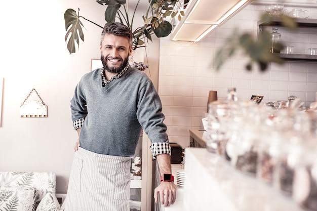 Właściciel stołówki. miły, zachwycony mężczyzna stojący przy blacie i uśmiechający się do ciebie
