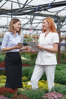 Właściciel szklarni przedstawia opcje kwiatów potencjalnemu sprzedawcy detalicznemu.