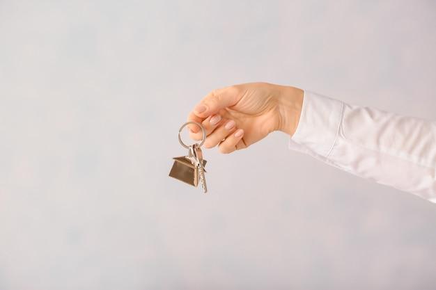 Właściciel z kluczami z nowego domu na jasnej powierzchni