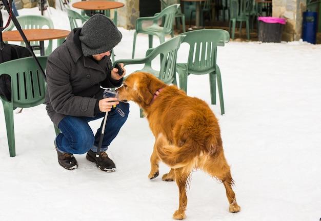 Właściciel zwierząt domowych, pies i ludzie koncepcja - młody uśmiechnięty mężczyzna kaukaski i pies odkryty w okresie zimowym.