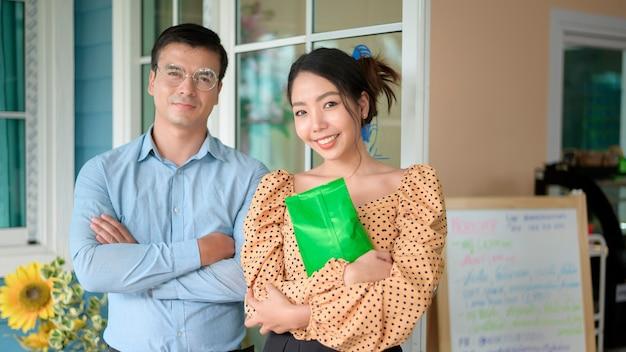 Właściciele firm analizują dane biznesowe, rozmawiają i uśmiechają się w nowoczesnym sklepie