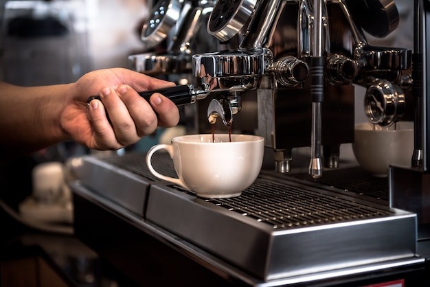 Właściciele kawiarni lub barista używający automatycznych ekspresów do kawy pracują na zasadzie destylacji skoncentrowanej wody kawowej, dla koncepcji biznesu i napojów.