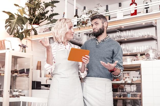 Właściciele kawiarni. mili, sympatyczni koledzy stoją w kawiarni, omawiając swoje pomysły na jej rozwój