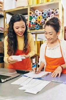 Właściciele kwiaciarni sprawdzający rachunki i rachunki podczas wypełniania raportu dla księgowego sprawdzającego dochody