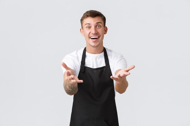 Właściciele małych firm, koncepcja kawiarni i personelu. przyjazny, szczęśliwy uśmiechnięty barista, przedsiębiorca kawiarniany w czarnym fartuchu, zadowolony, że widzi gości po zamknięciu covid-19, wyciągając ręce do przodu z radością