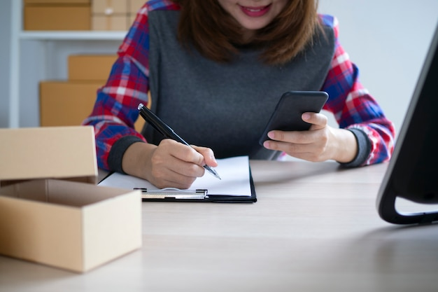 Właściciele małych firm piszą nazwiska, aby przygotować się do dostarczenia paczek klientom. małe firmy sprzedające online i zamawiające produkty online