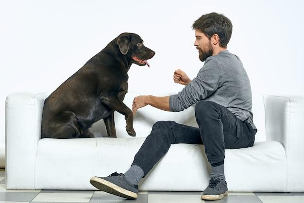 Właścicielka bawi się z psem na białej sofie