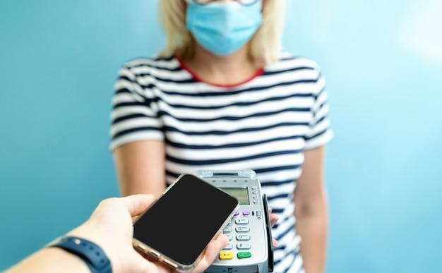 Właścicielka firmy rasy kaukaskiej otrzymuje płatność za pomocą zbliżeniowego smartfona.