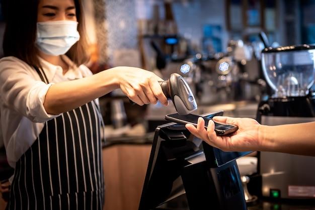 Właścicielka kawiarni, azjatka przyjmowanie płatności od klientów za pomocą skanera kodów kreskowych z aplikacją mobilną klienta do ludzi i nowego normalnego pojęcia.