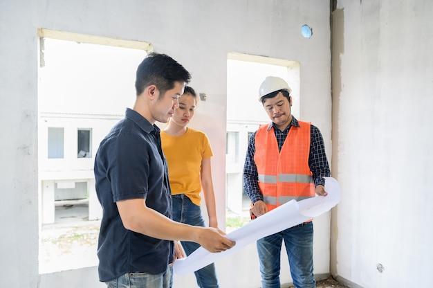 Właścicielka przeglądu nowego domu z inżynierem i architektem. zakochana para w projekcie wioski i budynku osiedla.