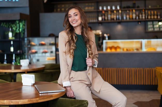 Właścicielka restauracji kobieta biznesu z laptopem w rękach ubrany elegancki kombinezon siedzący na stole w restauracji z blatem barowym kaukaski kobieta biznesmena wewnątrz