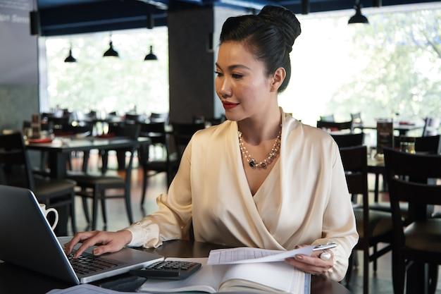 Właścicielka restauracji sprawdzająca raporty z danymi finansowymi i przygotowująca dokumenty dla działu podatkowego